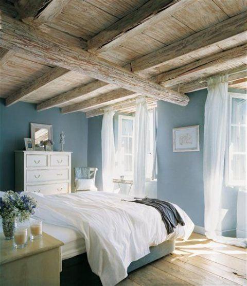 una camera da letto di ispirazione vintage con un soffitto in legno grezzo e rustico con molte travi che occupano lo spazio
