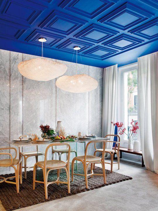 un soffitto rivestito di pannelli blu elettrico è una delle principali affermazioni di colore e caratteristica del design della sala da pranzo