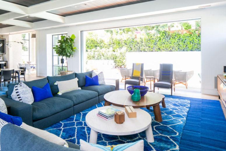 Il soggiorno è fatto con audaci blu e grigi e ci sono diversi tappeti per rendere più accogliente lo spazio