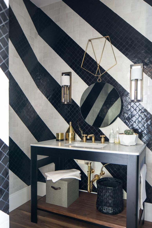 Il bagno è rivestito con piastrelle bianche e nere fatte a strisce