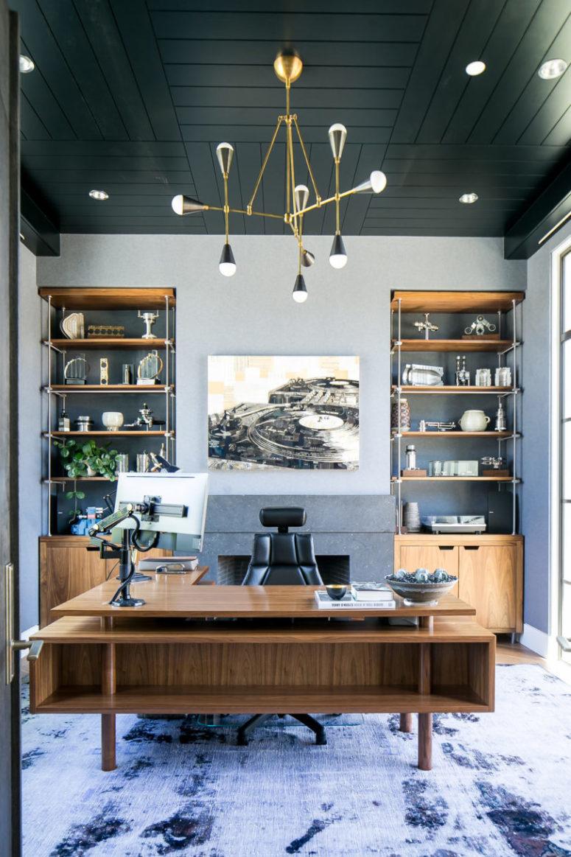 L'home office è fatto in grigio e blu, ci sono due pezzi di immagazzinaggio e una grande scrivania