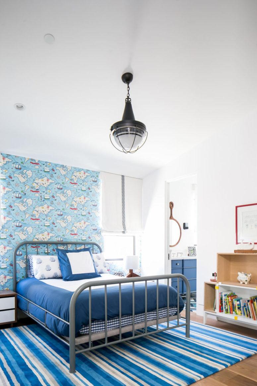 La camera da letto del bambino è realizzata con un tocco nautico, con carta da parati e tappeti accattivanti