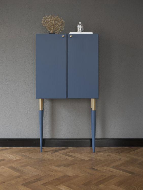un trucco molto chic e raffinato di un armadio Ivar in blu marino, con alte gambe dorate e blu scuro e manopole dorate