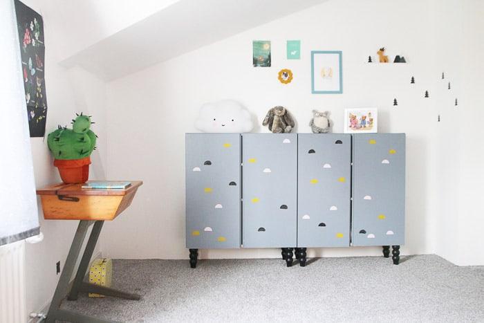 un mobile IKEA Ivar personalizzato con vernice grigia, stampe di nuvole e gambe nere per un asilo nido o una stanza dei bambini