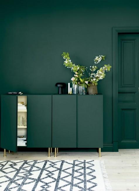 armadi Ivar verde scuro con gambe dorate davanti a una parete coordinata creano uno splendido spazio lunatico