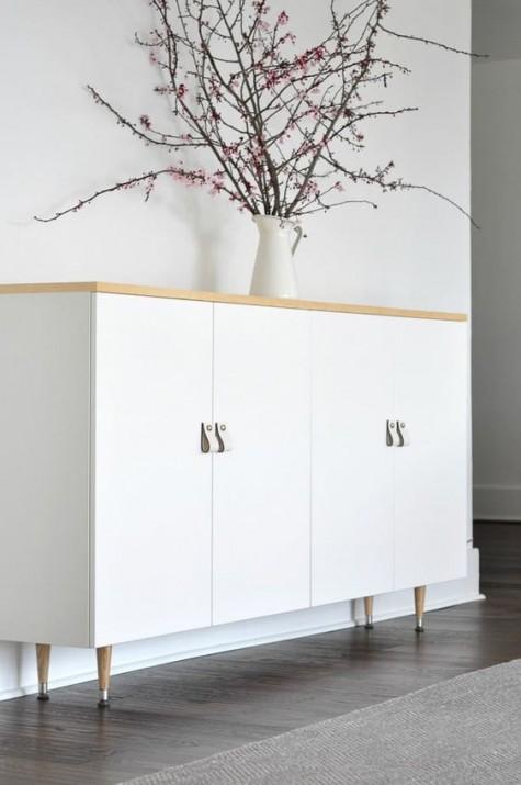 Gli armadietti Ivar bianchi con piano in legno e gambe in legno più maniglie in pelle bianca sembrano scandinavi