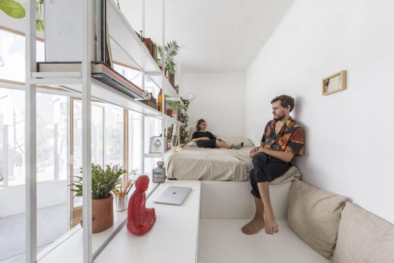 Questo è un angolo per dormire con un letto integrato e una piattaforma per lavorare, oltre ad alcuni ripiani ariosi e una scrivania