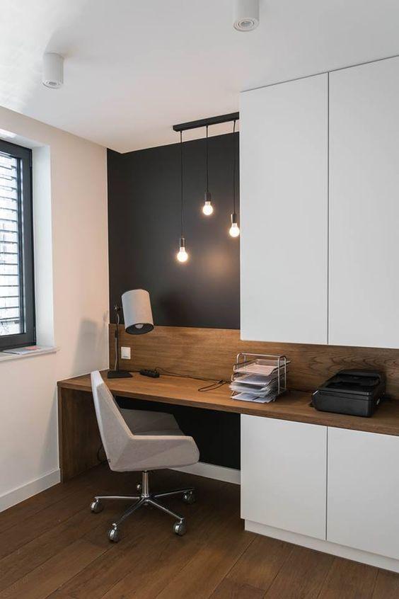 un angolo dell'ufficio domestico è visivamente separato dal resto dello spazio con un muro nero
