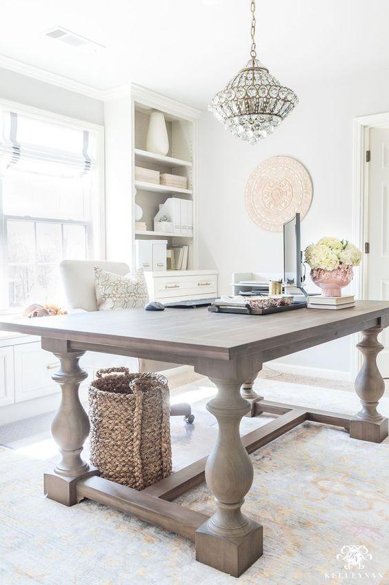 un tavolo vintage rustico sovradimensionato usato come scrivania sembra molto in contrasto con il moderno ufficio domestico