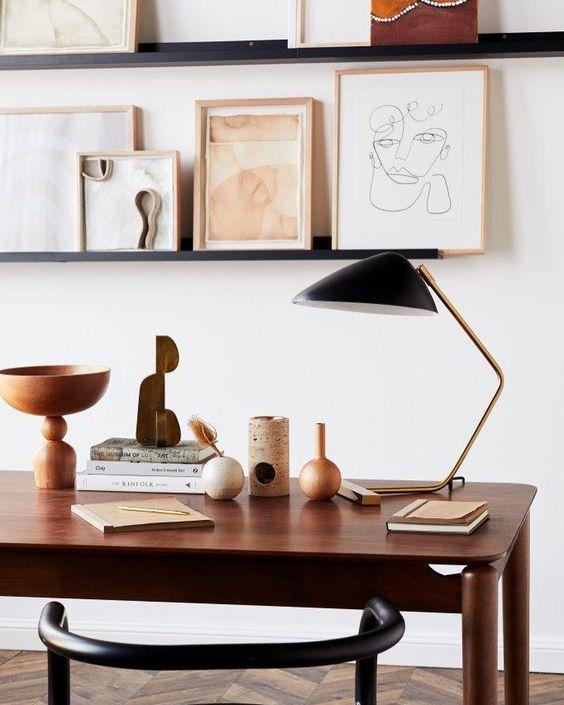 una galleria a parete creata su sporgenze di fronte alla scrivania è un'ottima idea, puoi anche usarli per riporre libri e documenti