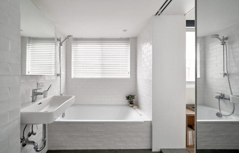 Il bagno è rivestito con piastrelle bianche, c'è una finestra coperta per avere luce naturale ma privacy
