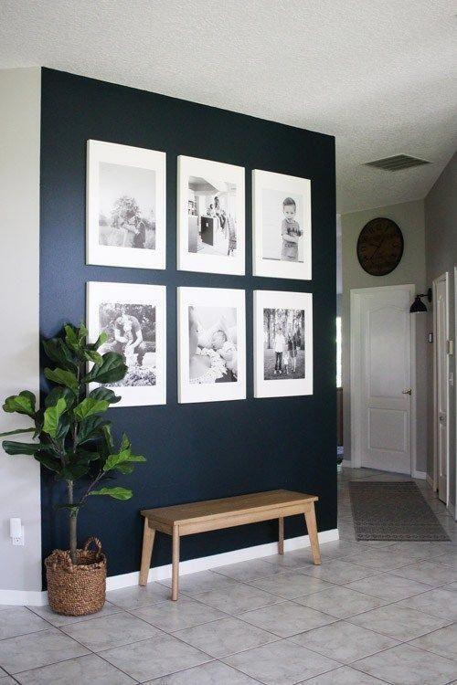 un muro blu navy con una galleria di foto di famiglia in bianco e nero