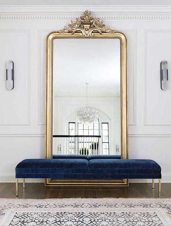 una bellissima panca in velluto blu scuro con gambe dorate è una dichiarazione raffinata e chic per l'ingresso