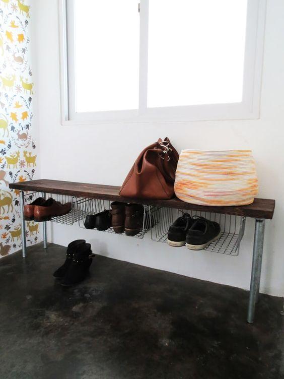 una panca da ingresso grezzo con gamba in metallo, un sedile in legno e cestini in filo metallico attaccati sotto il sedile