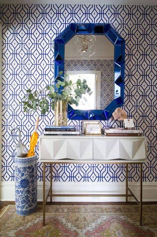 un audace muro di carta da parati stampato blu e un'urna e uno specchio abbinati per un effetto wow