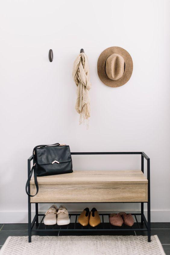 una piccola panca moderna con struttura in metallo nero e una grande seduta con contenitore nascosto