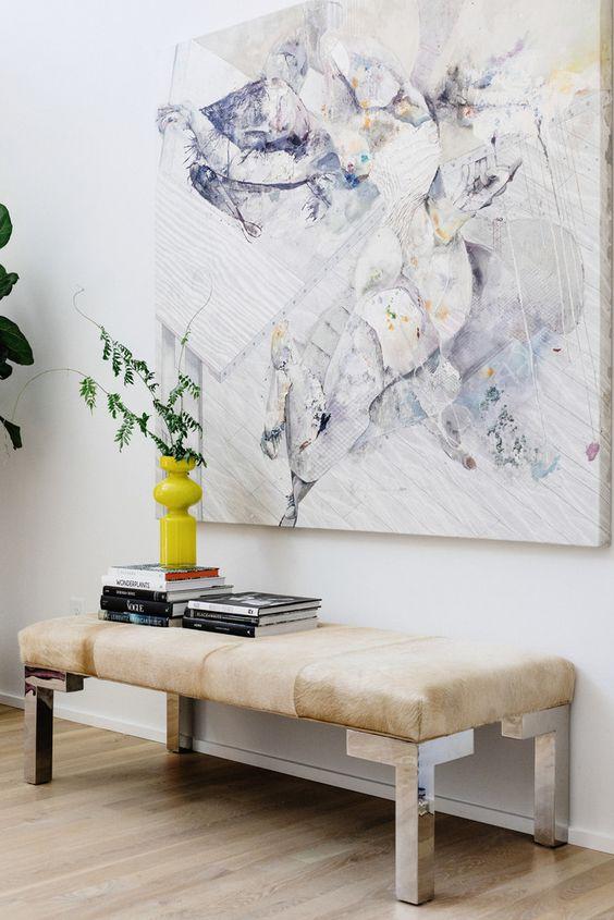 una panca moderna con gambe metalliche e un sedile imbottito in colore chiaro è un grande spazio