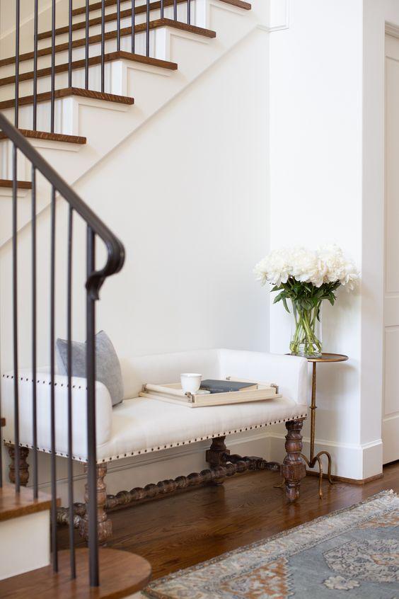 una raffinata panca vintage con una bella base in legno e un'elegante seduta imbottita
