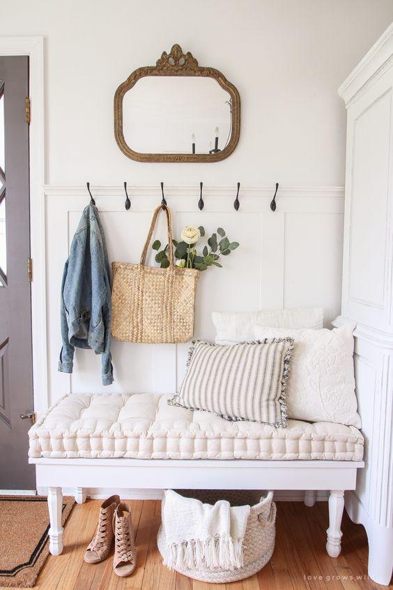 un'accogliente panca vintage con un cuscino super morbido dà un tono a questo ingresso