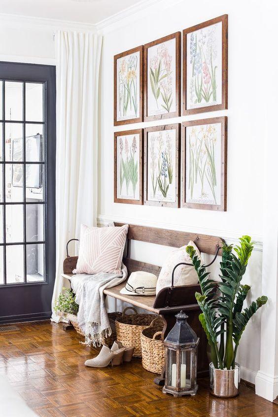 una galleria a parete con opere d'arte botaniche, piante in vaso, lanterne e cesti per accessoriare lo spazio