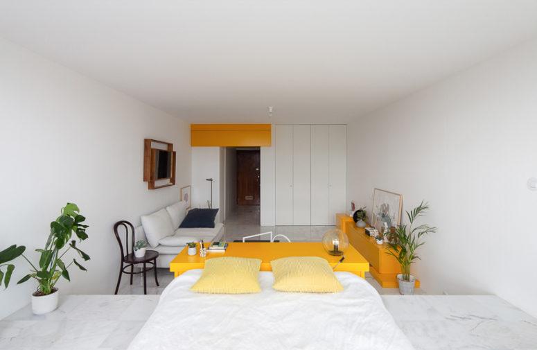Il soggiorno dispone di un divano neutro, una sedia nera e alcune piante in vaso