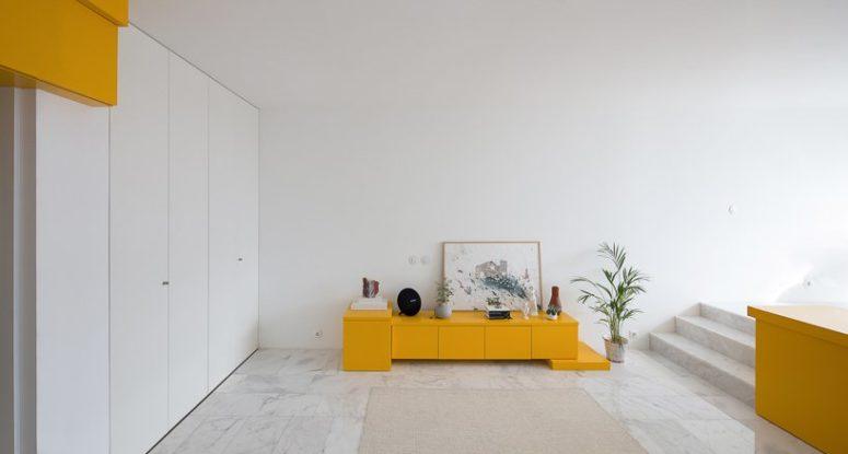 Un piccolo armadietto in giallo intenso nella zona soggiorno è ottimo anche per l'archiviazione