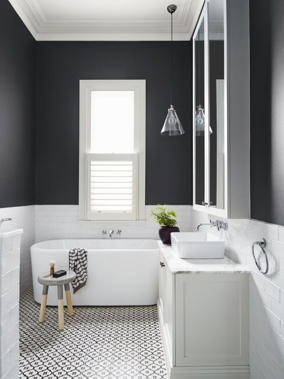 le pareti nere rivestite con piastrelle bianche creano un aspetto monocromatico ma accattivante e contrastante