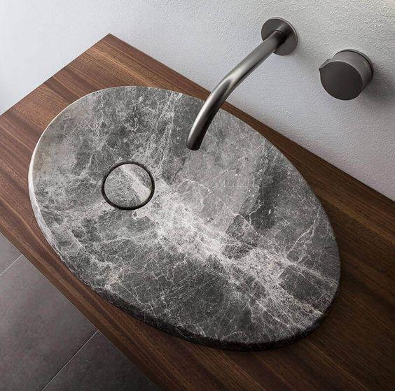 un fantastico lavabo moderno in pietra ovale per fare una dichiarazione in un bagno