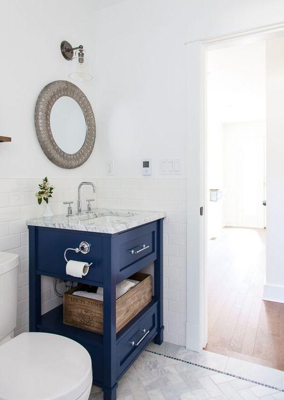 una piccola vanità blu brillante con un piano di lavoro in pietra e un po 'di spazio per riporre è una dichiarazione brillante