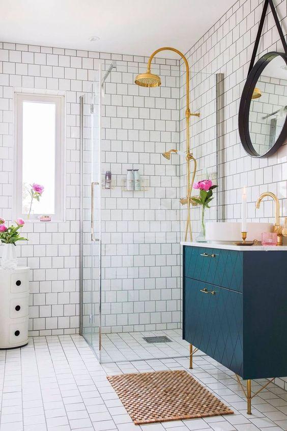 una splendida vanità geometrica blu con tocchi in ottone aggiunge colore al bagno neutro