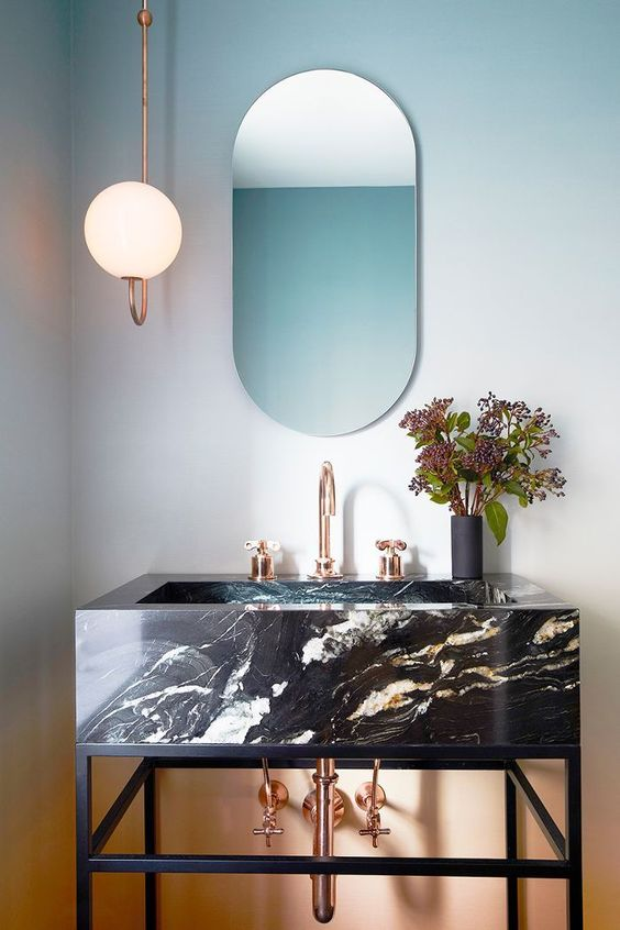 una spigolosa vanità in marmo nero che poggia su una vanità in acciaio annerito e accessoriata con tocchi di rame