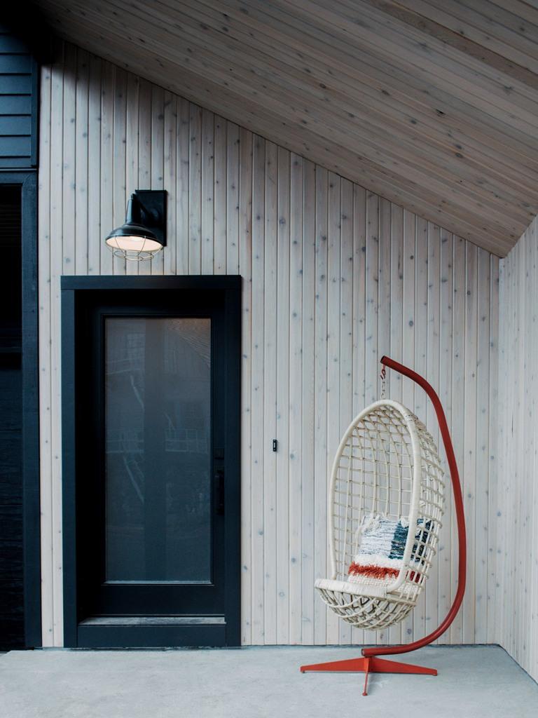 Il portico è rivestito di pino di colore chiaro e c'è una sedia a sospensione accattivante
