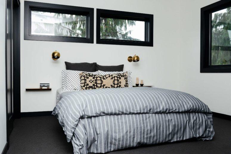 La camera da letto principale è realizzata con tocchi di nero per più dramma e un letto con comodini galleggianti