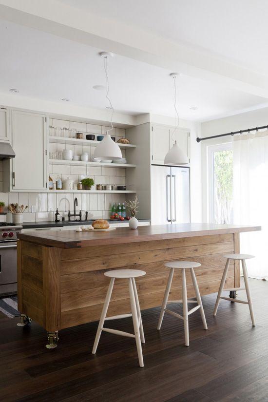 una grande isola cucina rivestita in legno contrasta con la cucina neutra