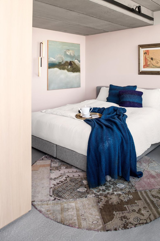 La camera da letto principale è realizzata con pareti arrossate, un comodo letto grigio e alcune opere d'arte