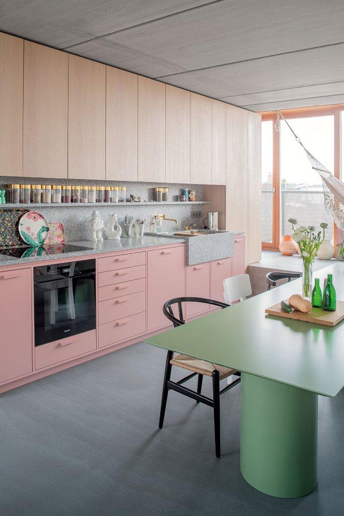 La cucina è realizzata con armadi in legno e rosa e un piano di lavoro in terrazzo e alzatina