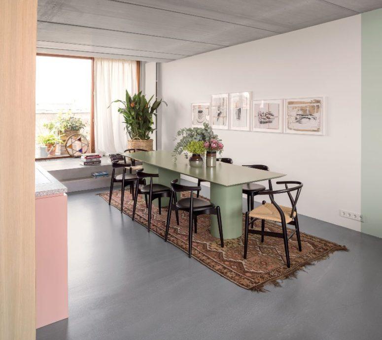 La sala da pranzo è arredata con sedie nere e un tavolo verde pastello più opere d'arte