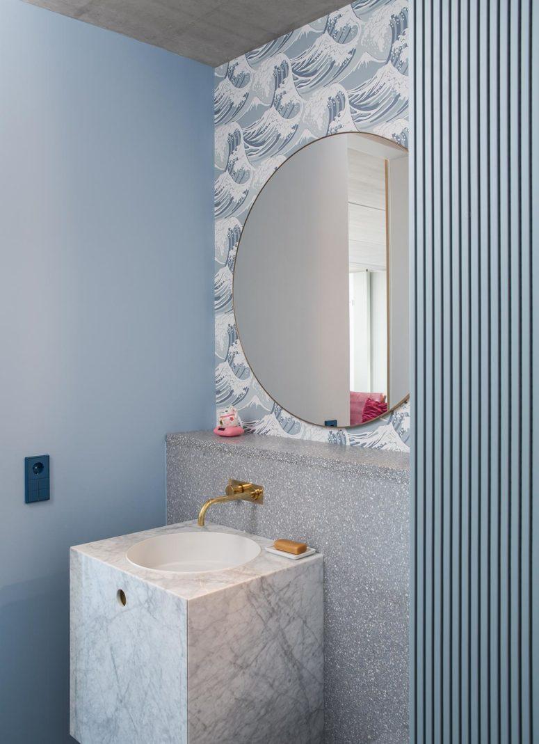 Il bagno è caratterizzato da grigi e blu, c'è pietra, terrazzo, carta da parati e vernice per portare più trame