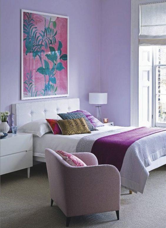 una camera da letto luminosa con pareti lilla, una sedia rosa e lenzuola e cuscini luminosi è un ottimo posto per svegliarsi