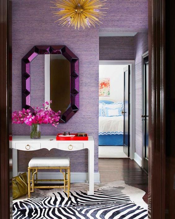 un ingresso luminoso con pareti di carta da parati lilla e uno specchio viola, i tocchi dorati aggiungono un tocco glam allo spazio