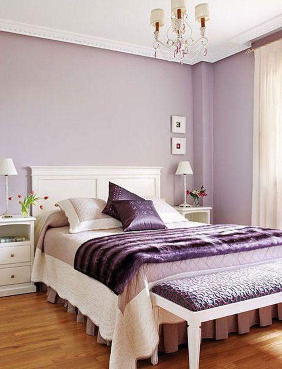 una camera da letto femminile con pareti lilla, accessori viola e una panca imbottita è un'idea chic e raffinata