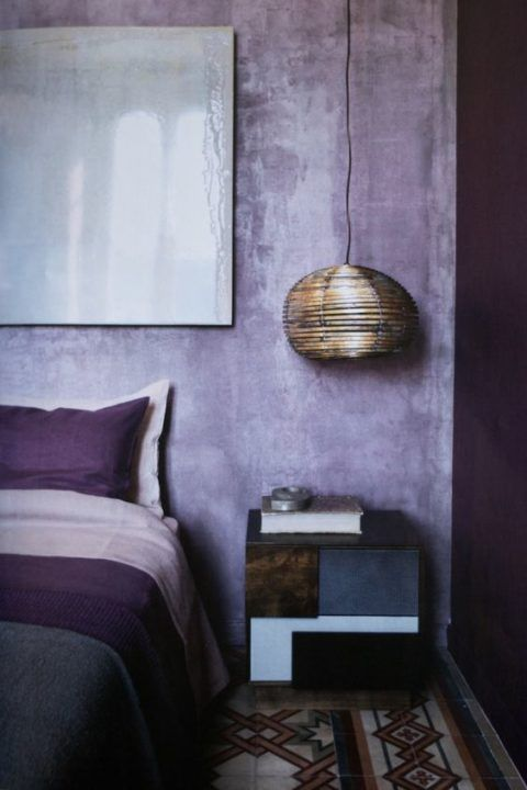 pareti in gesso lilla e tocchi di viola intenso compongono una camera da letto audace e ultra moderna