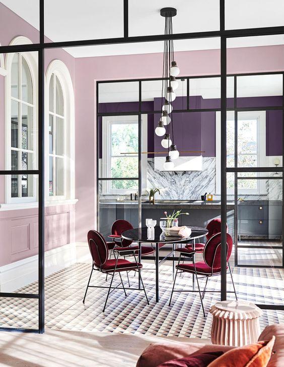 una cucina con pareti viola e armadi grigi e una sala da pranzo accentata con pareti lilla per separarla dalla cucina