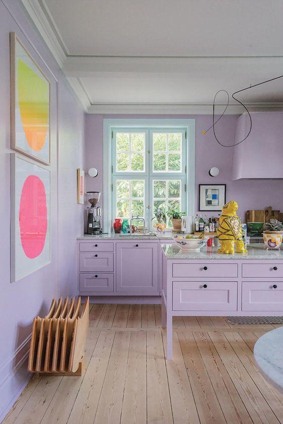 una tenera cucina lilla con brillanti opere d'arte astratte è uno spazio molto femminile e accogliente