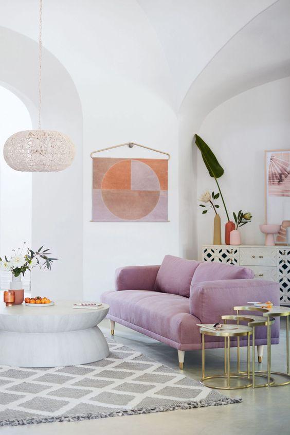 un soggiorno contemporaneo fatto in neutri e con un divano lilla come tocco luminoso e centrotavola