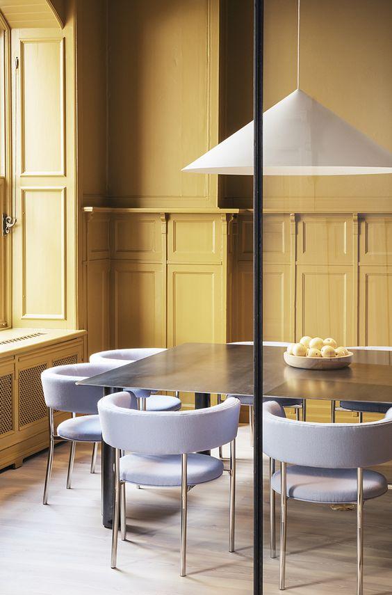 una sala da pranzo con pareti gialle e sedie lilla e ottone dal design laconico e moderno