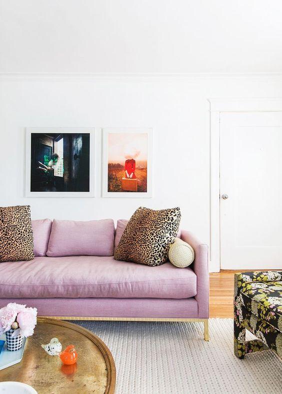 un divano lilla e oro e cuscini leopardati come accessori creano un look audace e una dichiarazione di colore