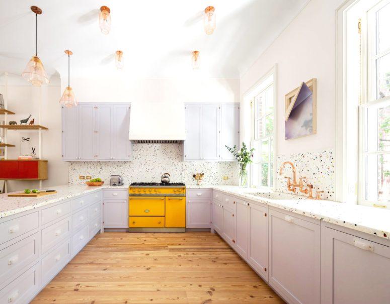 una cucina lilla accentata con un fornello giallo brillante e un backsplash a pois più lampade in ottone