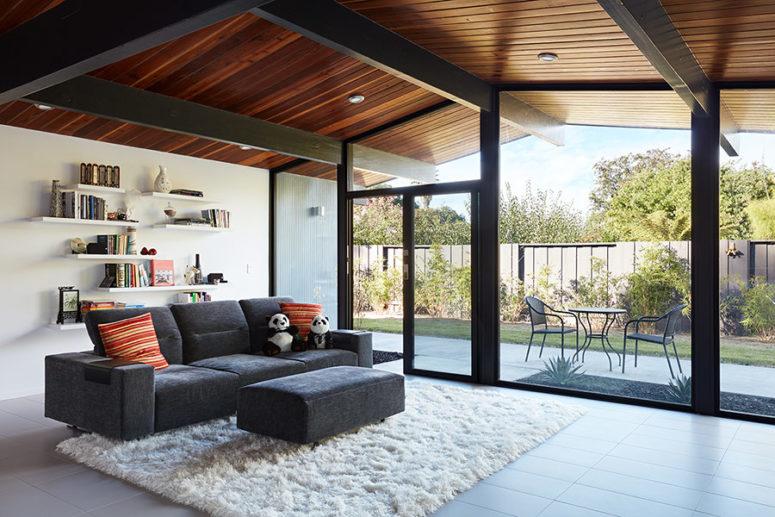Il soggiorno è fatto con un divano grigio, un pouf, alcuni scaffali aperti e un soffice tappeto