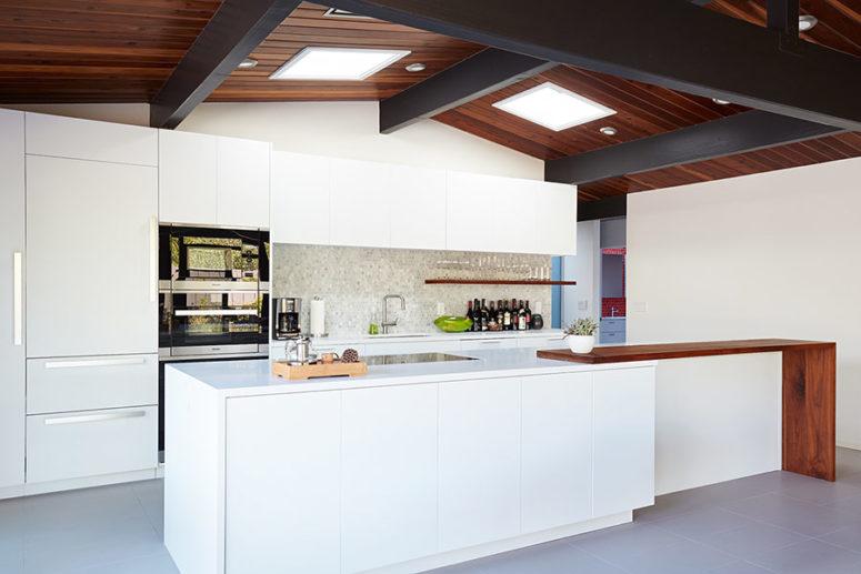 La cucina è realizzata con mobili bianchi eleganti, un backsplash in piastrelle di marmo